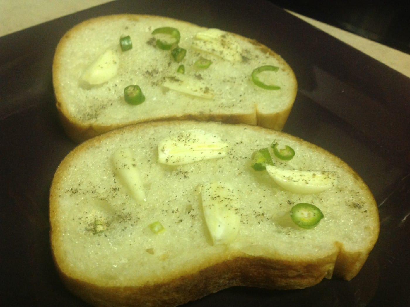 Overhead view of 2 pieces of toast on bread with garlic and chopped Thai chili