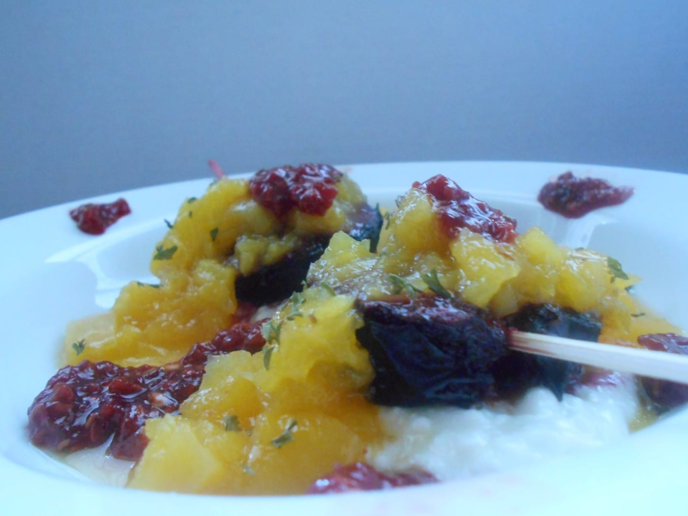 Side view of roasted plums on cottage cheese and topped with mango compote