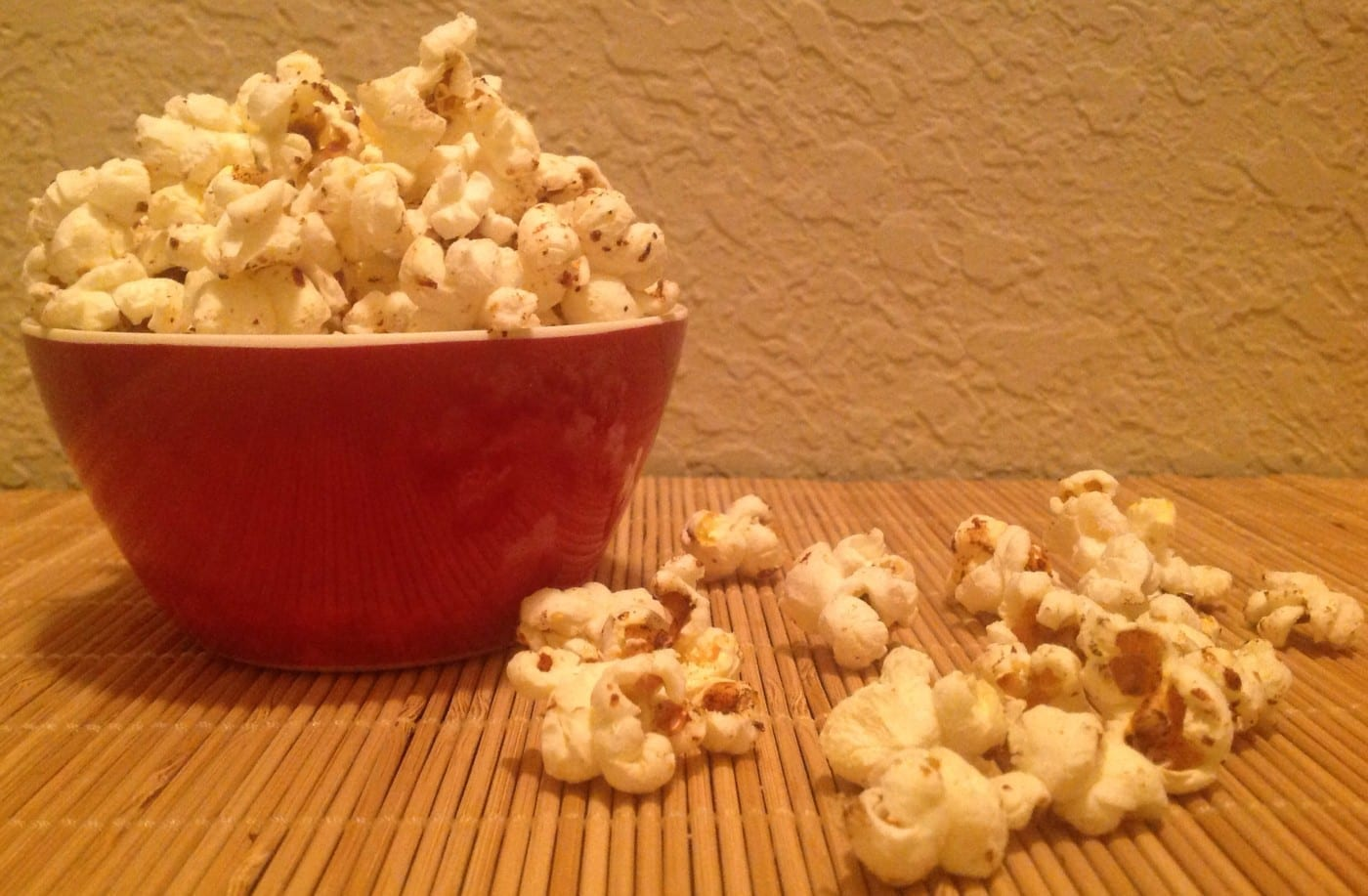 Tomato flavored gourmet kettle corn popcorn in a red bowl on a bamboo mat