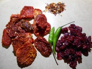 Top view of ingredients for the sun-dried tomato spread on a white plate