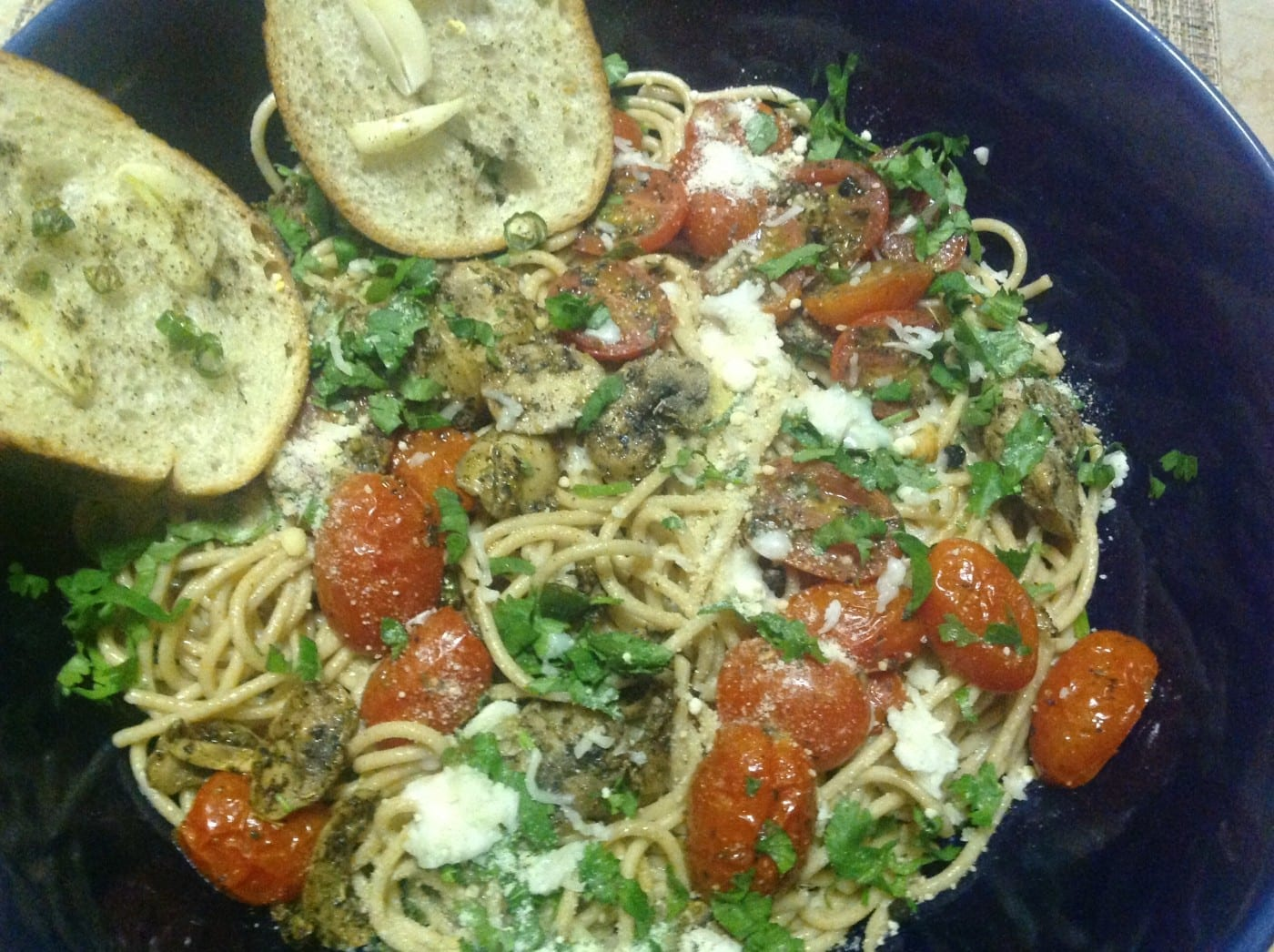 Closeup view of a blue bowl with spaghetti, roasted tomatoes and garlic toast on the side