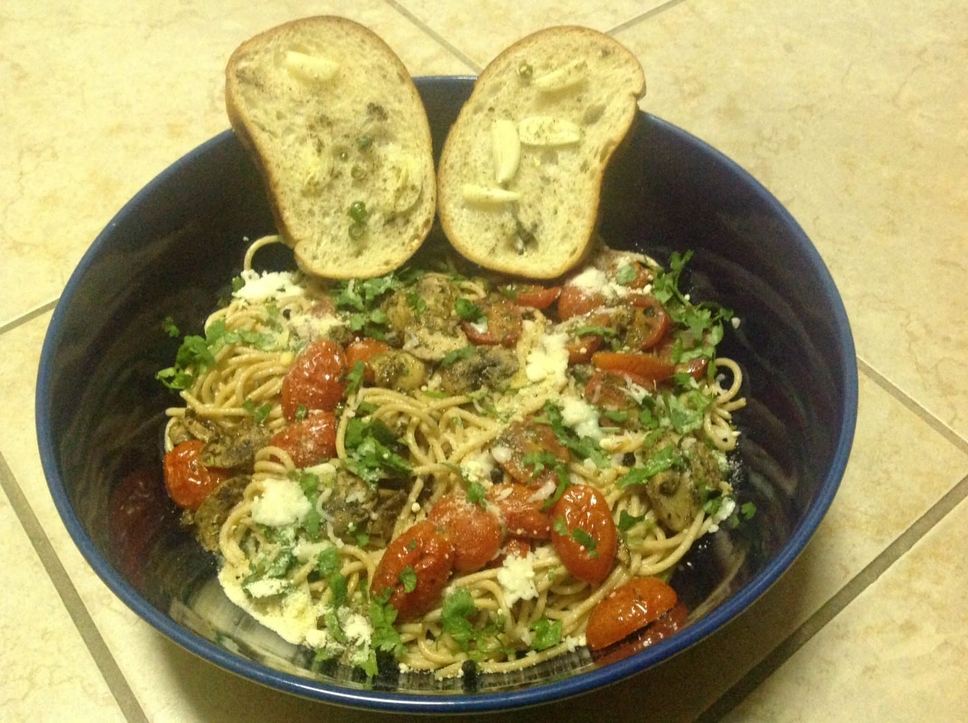 Overhead view of a blue bowl with spaghetti, roasted tomatoes and garlic toast on the side