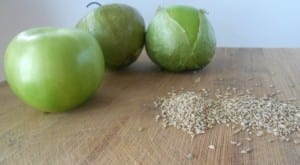 green tomato and carom seeds on a brown chopping board
