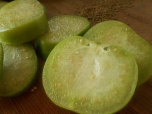 Sliced green tomatillo and carom seeds