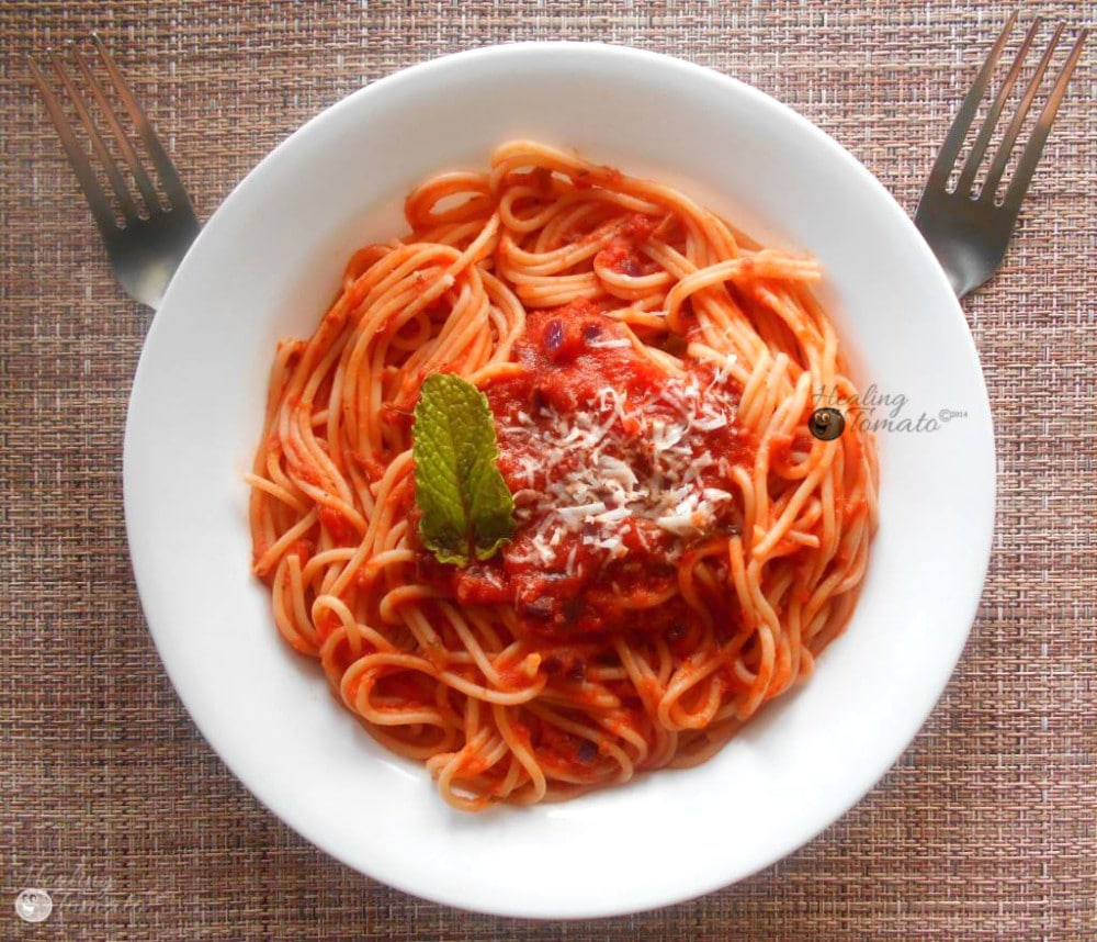 Overhead view of a bowl of pasta with Marinara sauce and two forks on the side