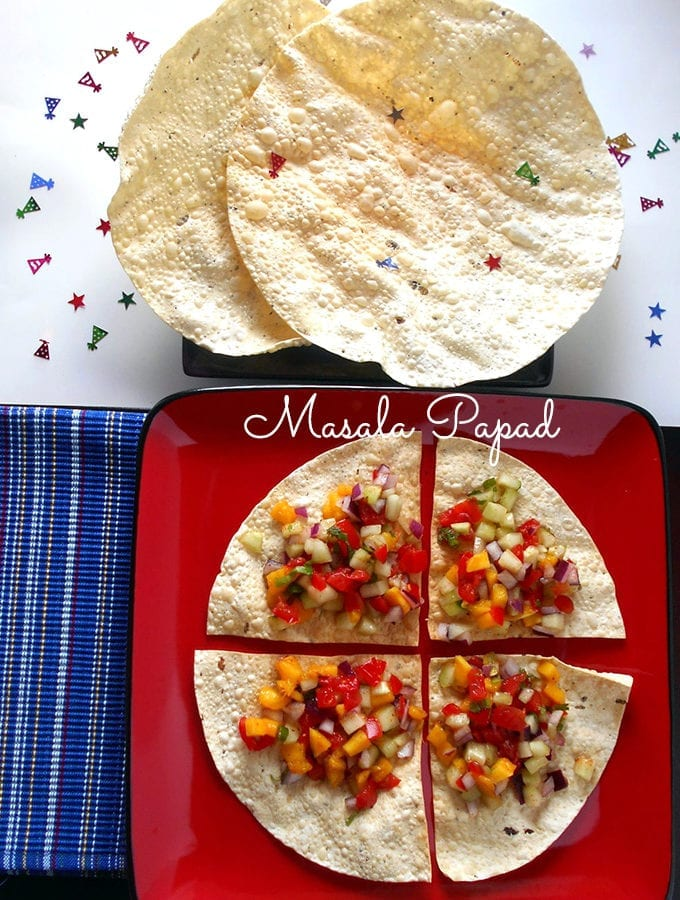 Overhead View of A Square Red Plate with Papad Cut into Quarters and Topped with Mango, onions and Red Peppers
