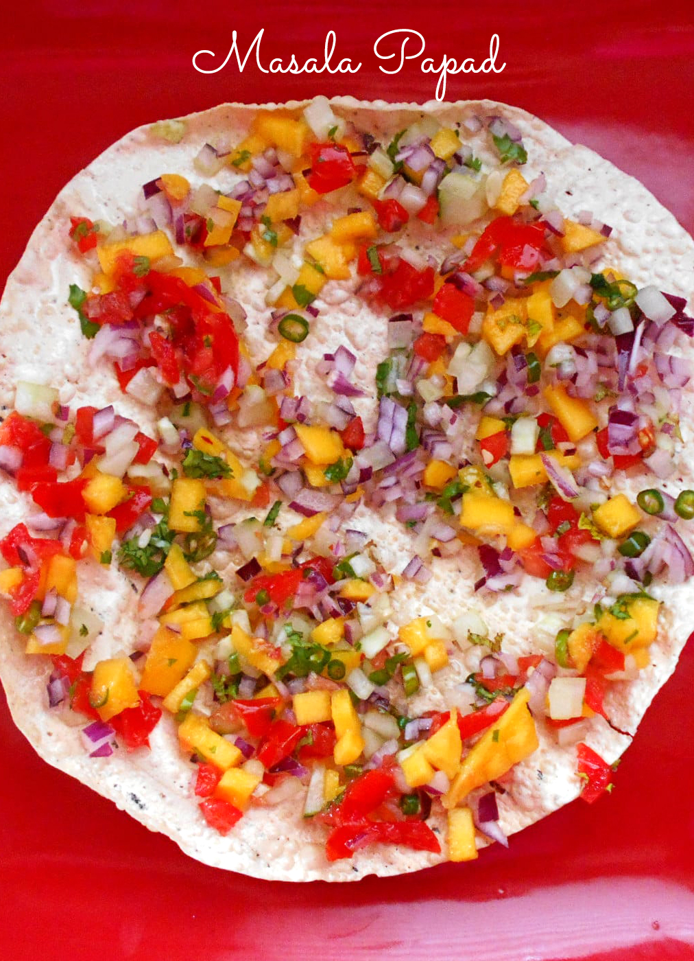 Closeup View of A Square Red Plate with Papad Cut into Quarters and Topped with Mango, onions and Red Peppers