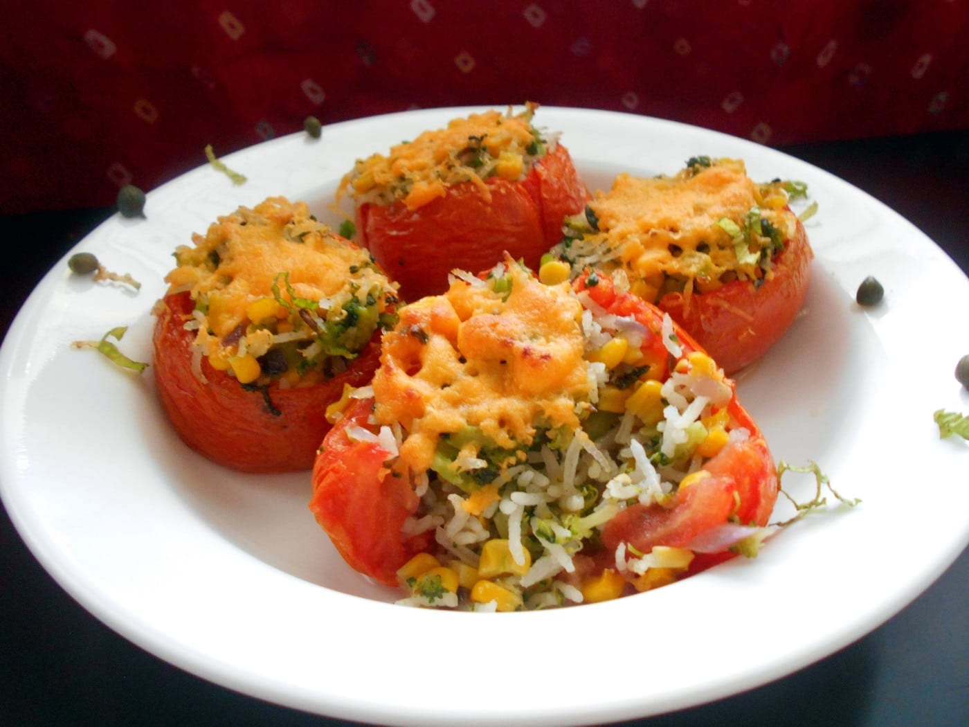 Cooked Stuffed Tomatoes on a white plate with garnish