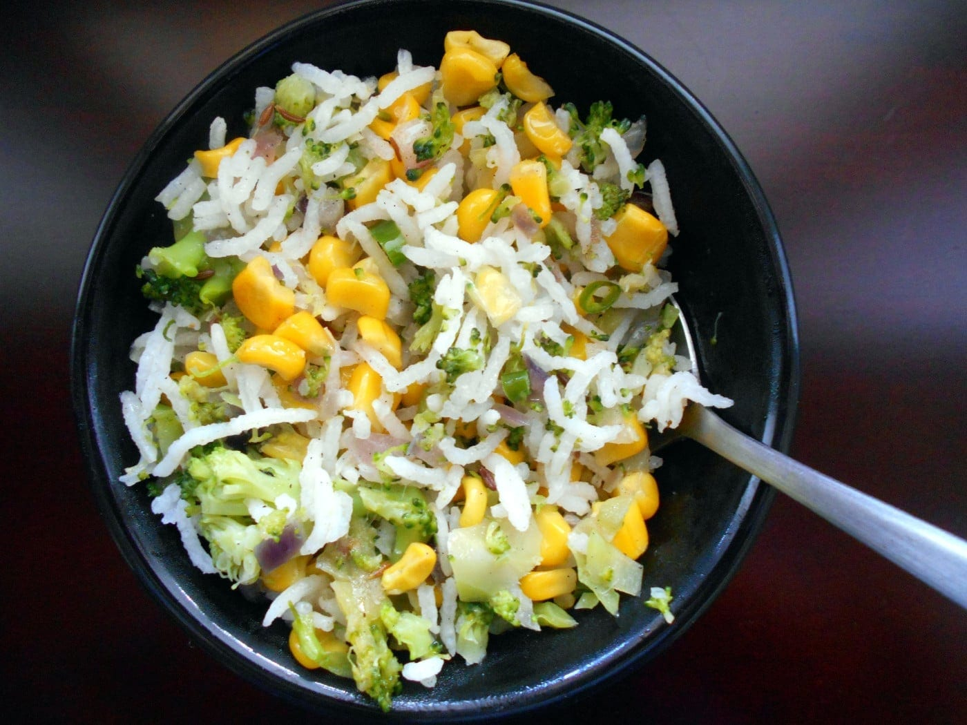 A small black bowl with rice, corn and broccoli with a spoon