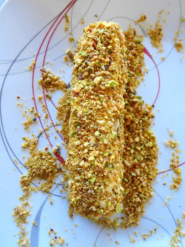 Overhead view of a goat cheese salad coated in pistachio and cardomom crumbs - Goat Cheese Salad