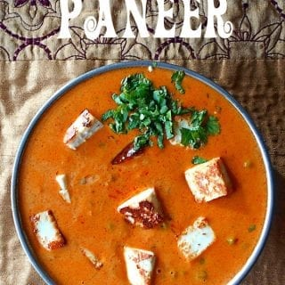 Overhead view of a thick, creamy tomato sauce with roasted paneer and peas