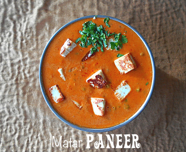 Closeup view of a thick, creamy tomato sauce with roasted paneer and peas - Matar Paneer
