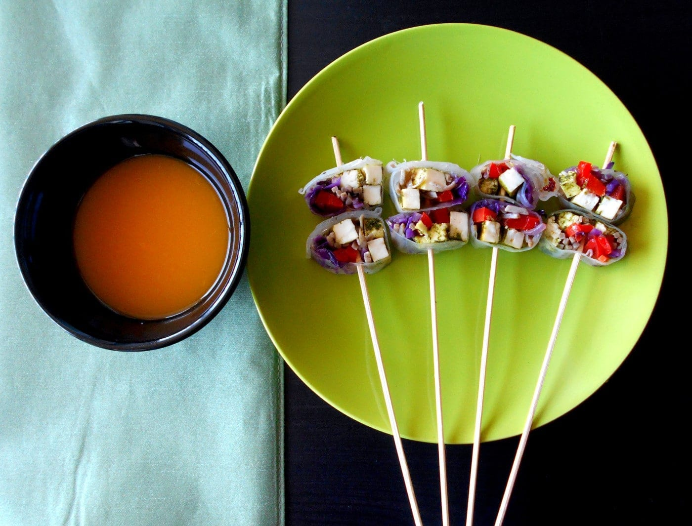 Top view of vegetarian rolls on sticks with apricot dressing on the side