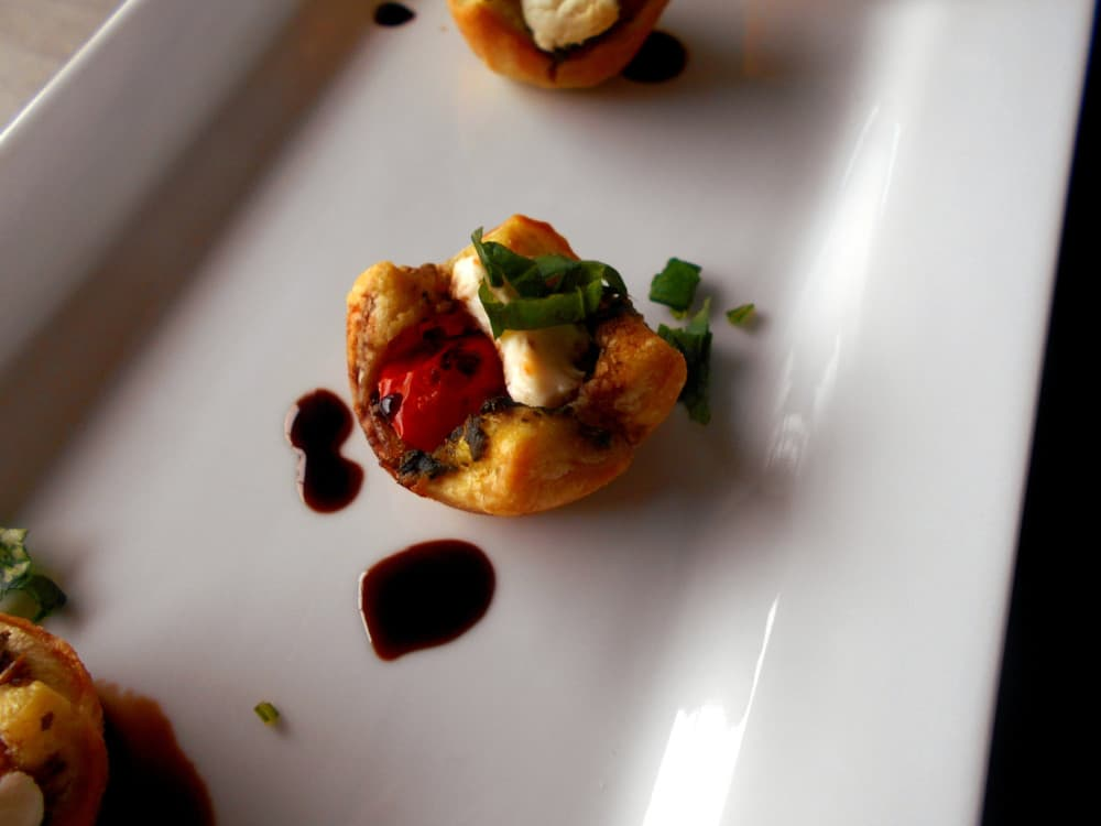 Caprese Salad Bites in a Puff Pastry Cup. Perfect bite-sized appetizers for any occasion. The Pesto acts as a base. Top with a balsamic vinaigrette reduction sauce. Quick and easy recipe