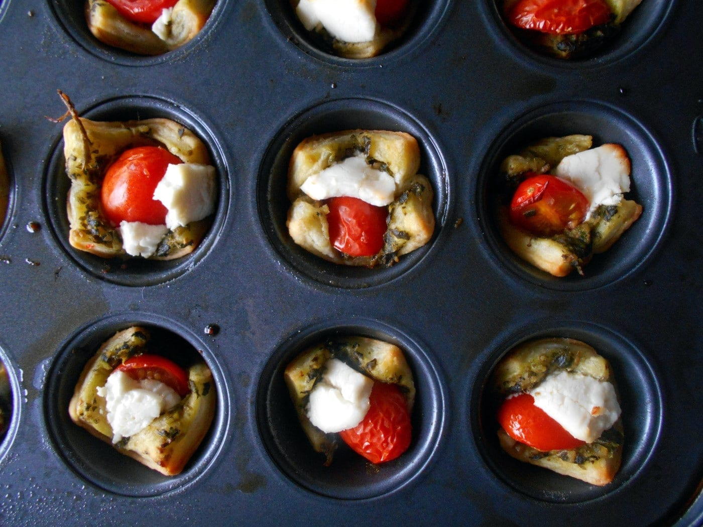 Caprese Puff Pastry Bites. Perfect bite-sized appetizers for any occasion. The Pesto acts as a base. Top with a balsamic vinaigrette reduction sauce. Quick and easy recipe