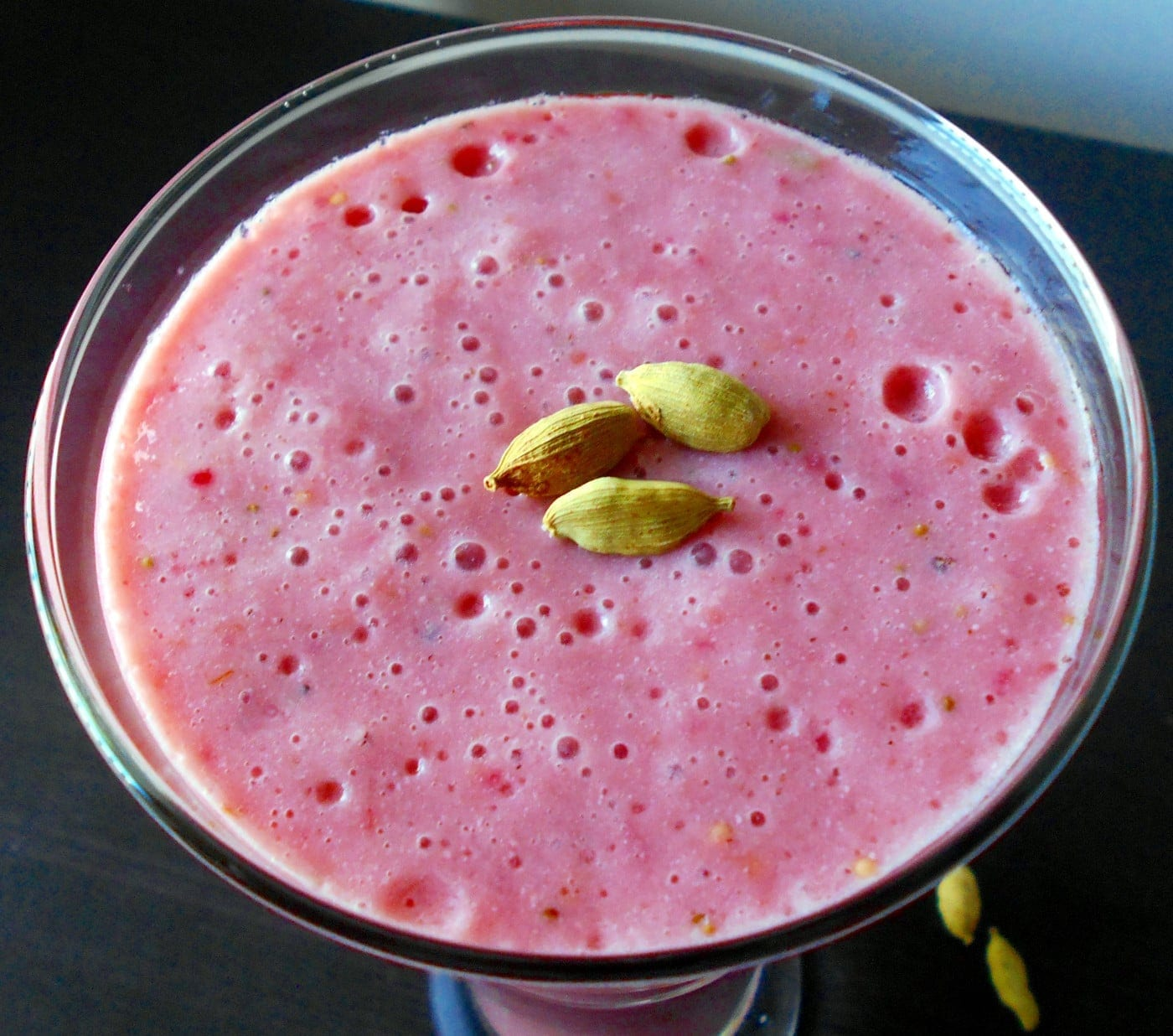 Closeup view of the top of the glass filled with  Tomatillo Strawberry Smoothie