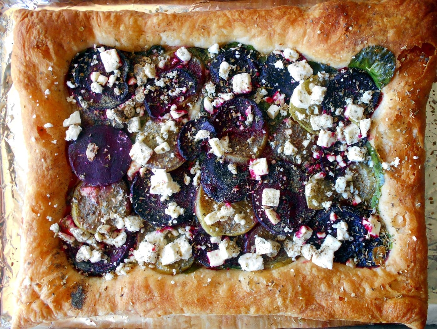 Overhead view of a wholly baked puff pastry beet tart that is oven roasted