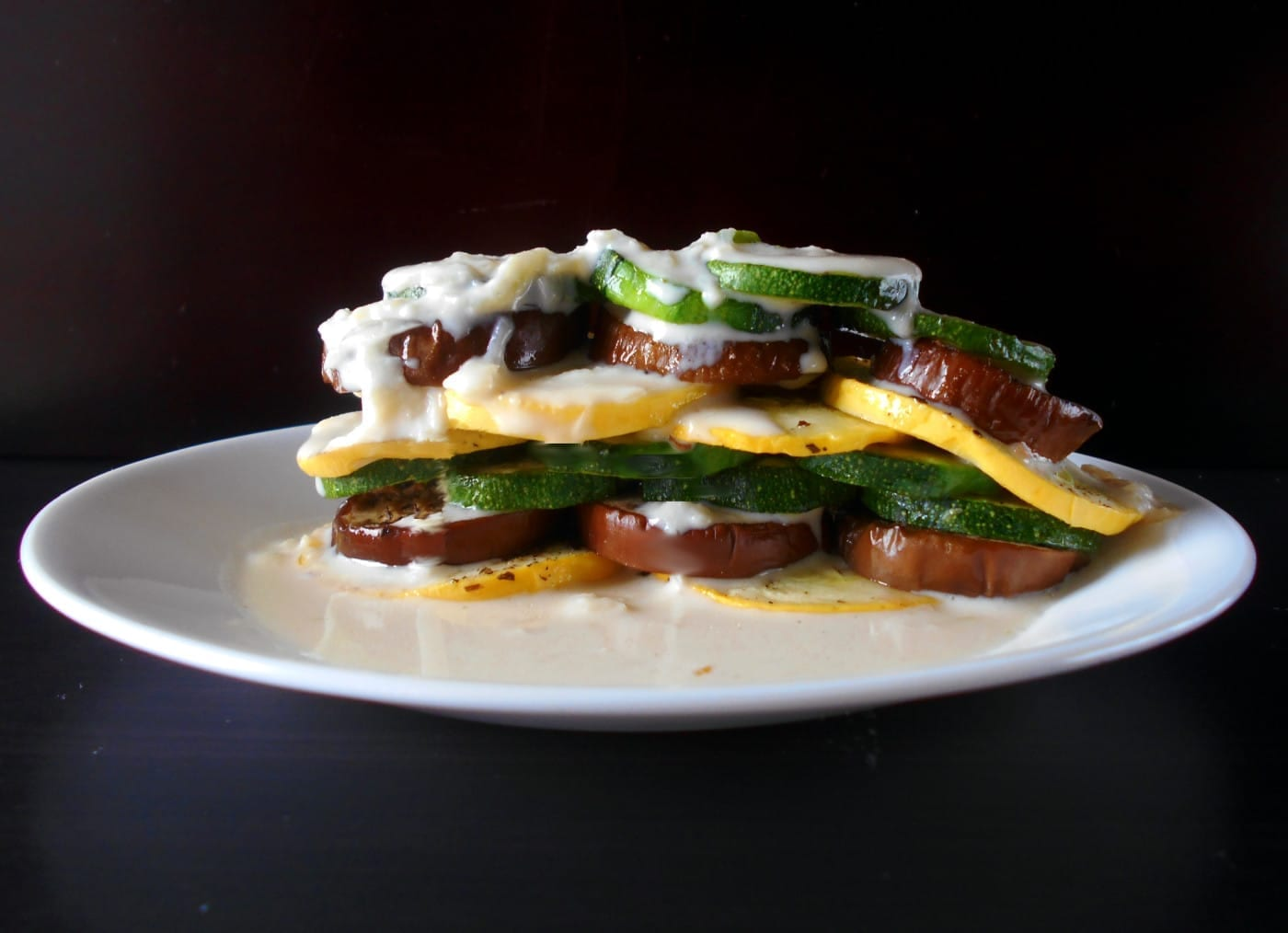 Front view of a stack of fresh veggies doused with soubise sauce - Ratatouille Stack