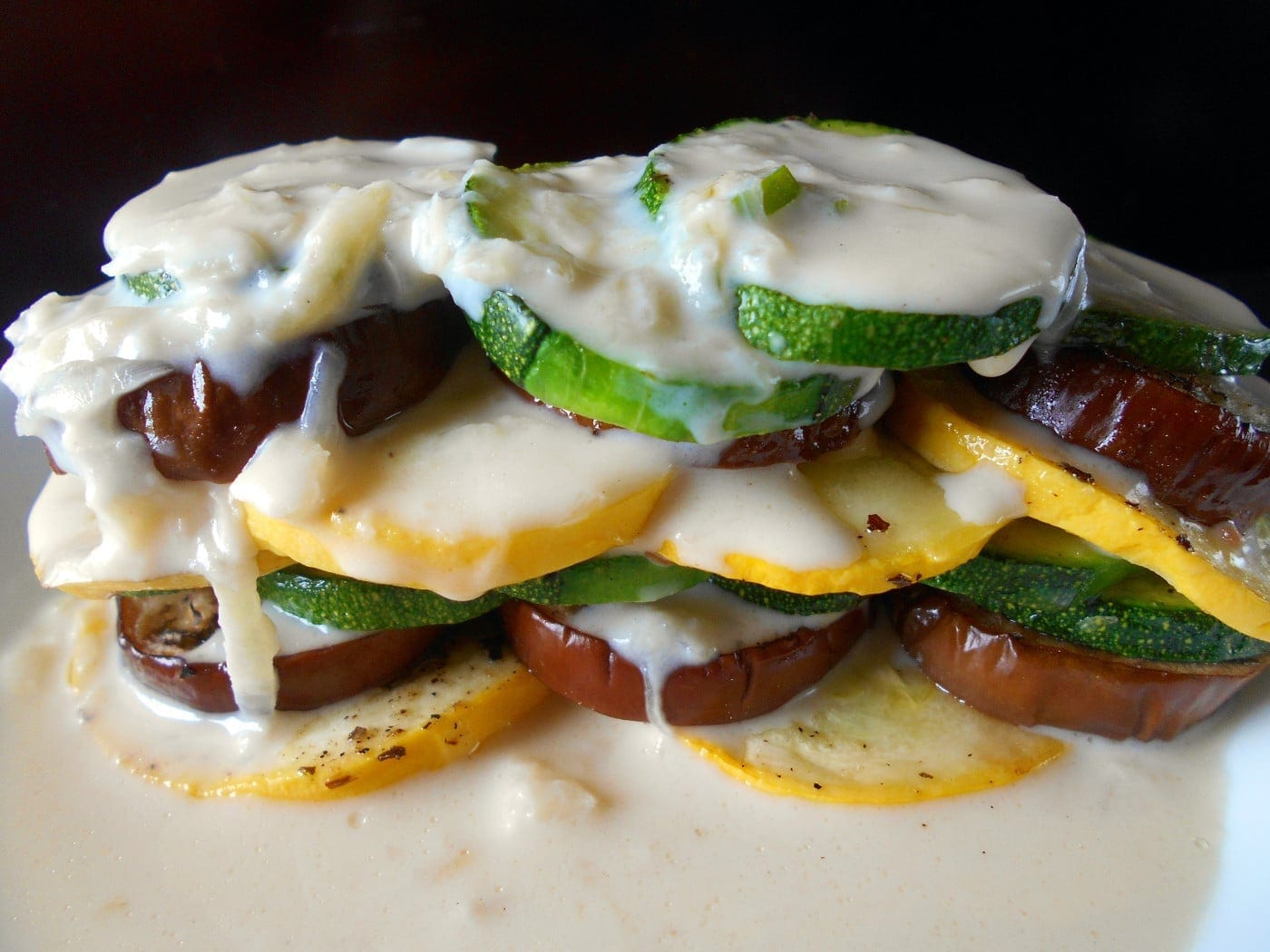Closeup view of a stack of roasted vegetables doused with soubise sauce - Ratatouille Stack
