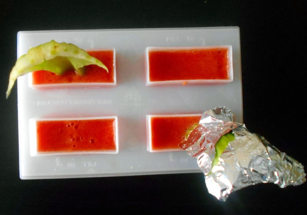 Overhead view of a popsicle mold with bloody mary popsicle and celery sticks as sticks