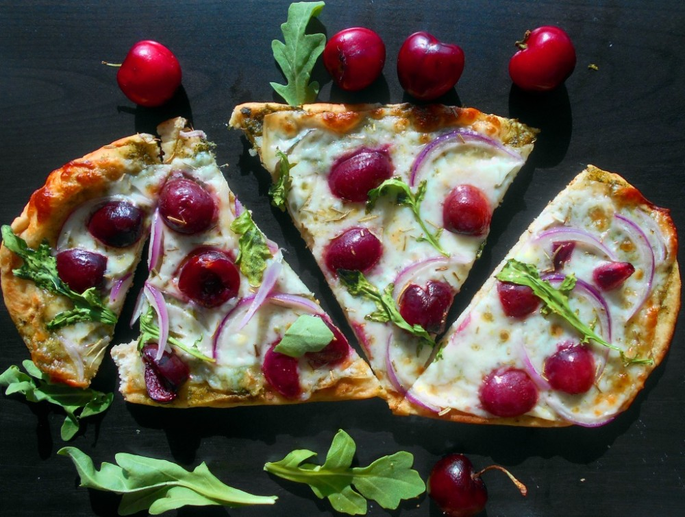 Top view of cherries on flatbread pizza