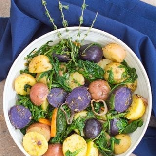 Overhead view of white bowl with a blue napkin wrapping most of the bowl. Bowl filled with multi colored potatoes, sautéed greens, carrot shavings, grilled shallots and pesto sauce.