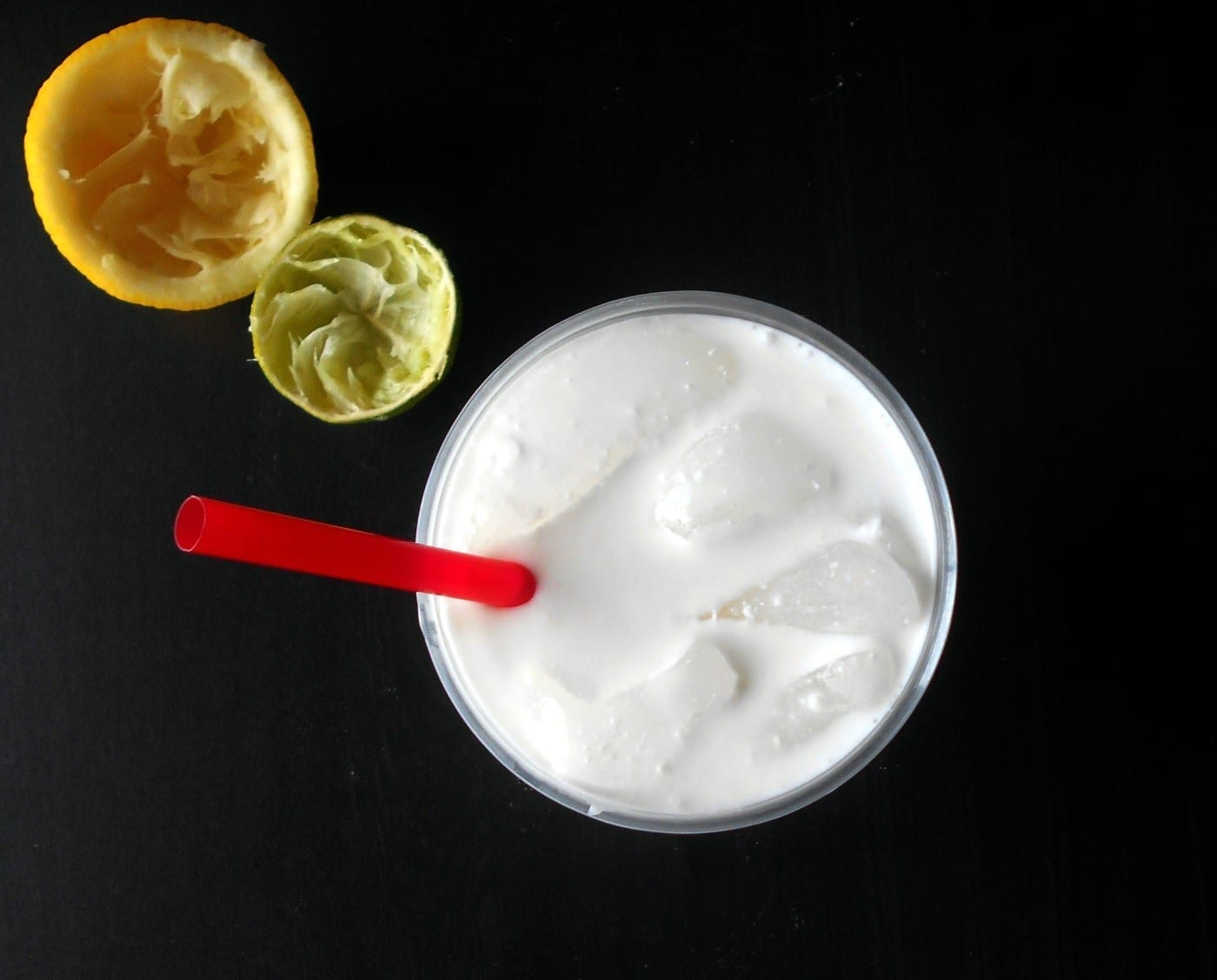 Overhead view of white lemonade with red straw and ice cubes. A side of squeezed lemons and lime on a black background