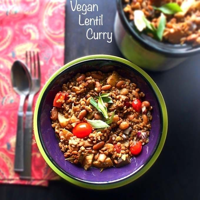 Overhead view of a blue bowl on a green plate filled with vegan lentil curry. On the top left, a mini slow cooker filled with the same curry is visible. To the left, a spoon and a fork are on top of a folded red cloth