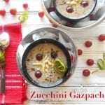 Overhead View of a Small Black Bowl with Cream Colored Zucchini Gazpacho Garnished with Grapes and Slivered Almonds. Black Bowl is on Top of a Slightly Larger Stainless Steel Bowl Filled With Ice Cubes. On the Left Side, a Spoon Sits On Top of a Light Red Napkin. On the Top Right Corner Is a Similar 2 Bowl Setup that is Partially Visible. A Few Grapes are Strewn About in the Picture. Zucchini Gazpacho is Written in Didot Font at the bottom of the Photo.