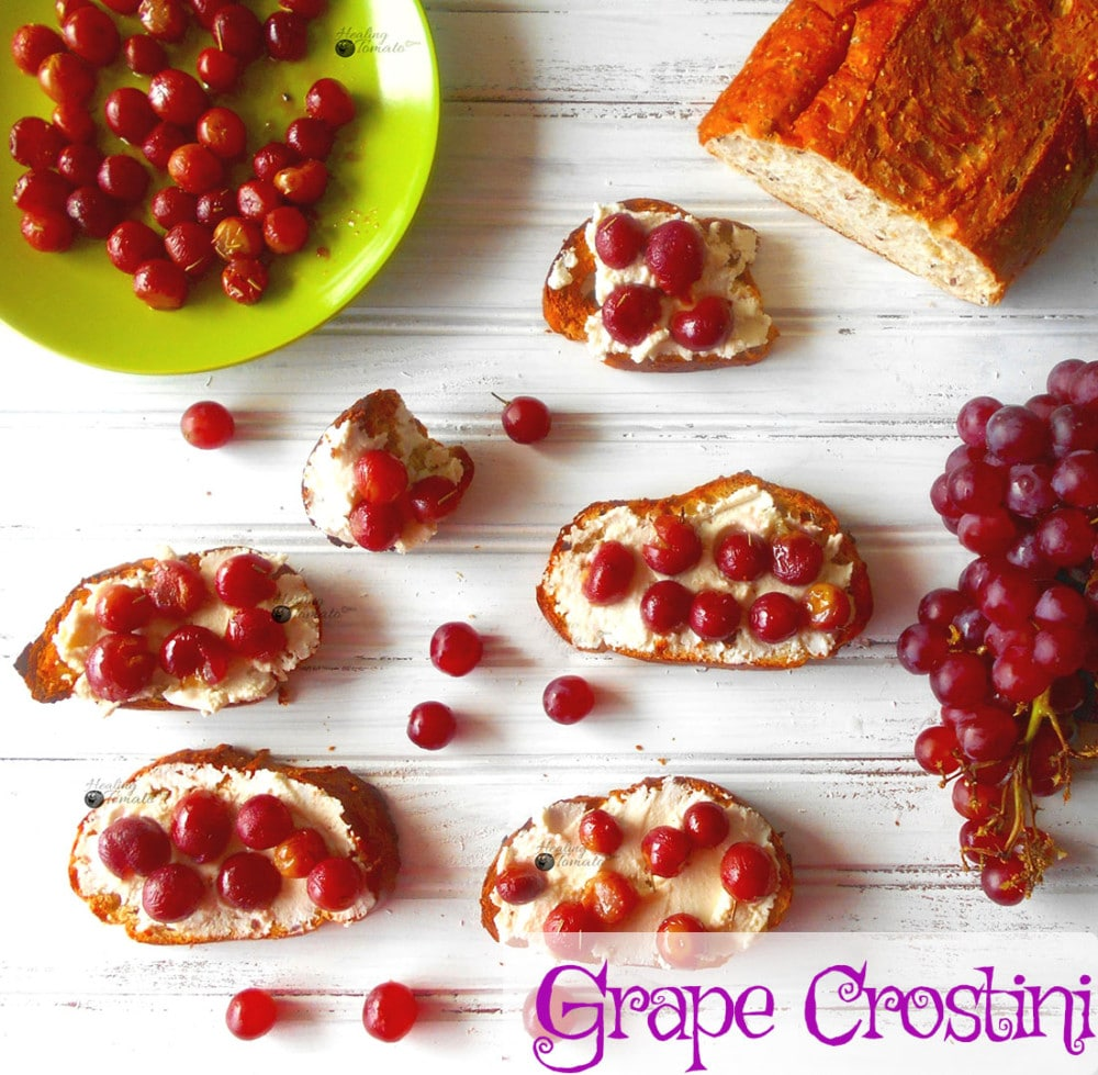 Overhead view of several grape crostinis with a bunch of grapes on the side