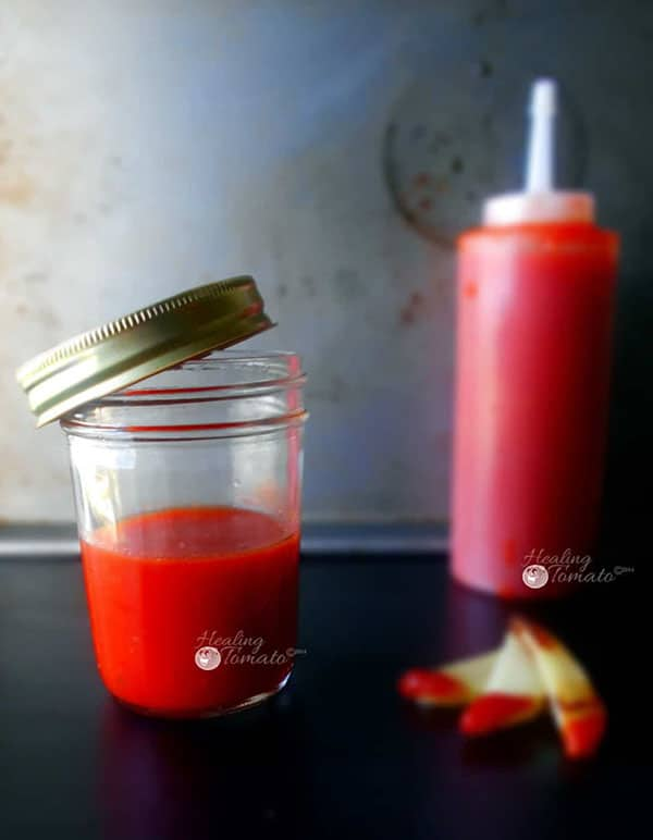 A mason jar with homemade ketchup recipe and a ketchup bottle in the background