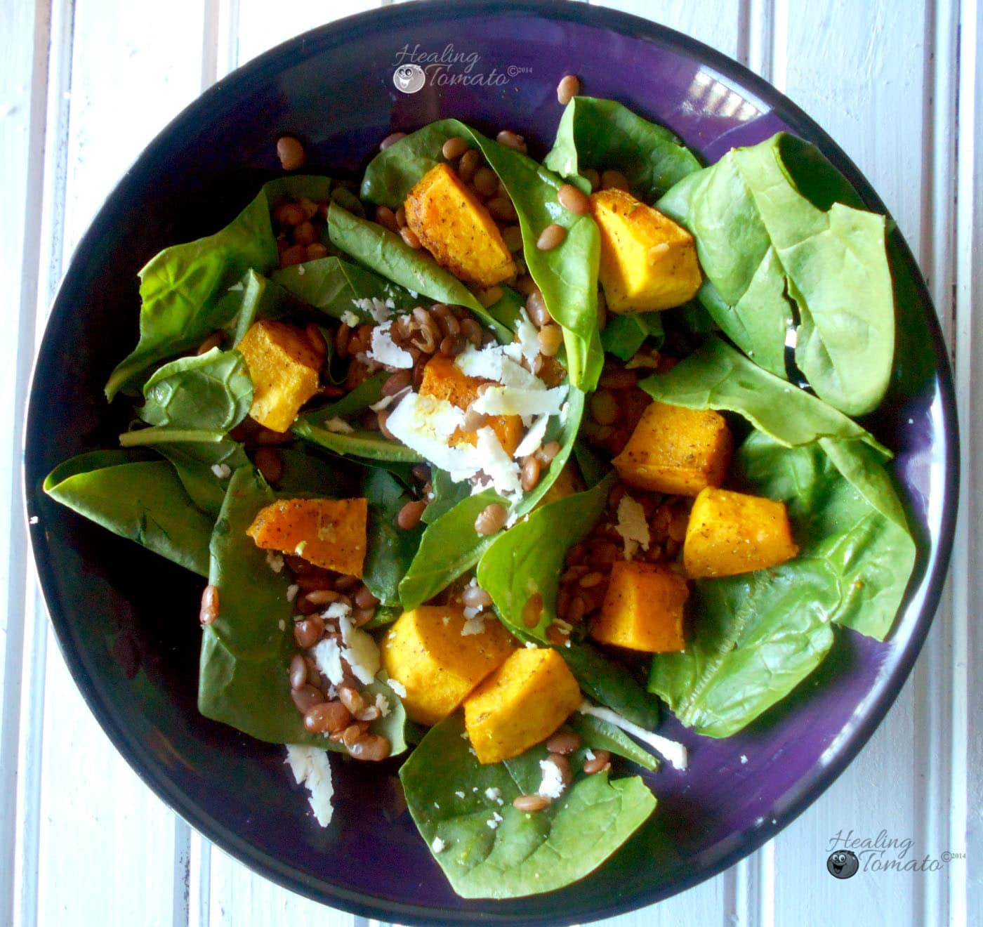 Closeup view of spinach lentil salad withspiced pumpkins