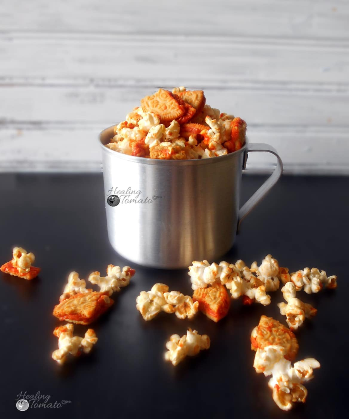 Front view of stainless steel milk container filled to the top with pumpkin spice popcorn