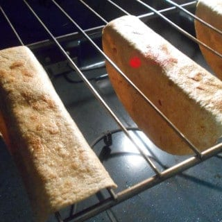Oven View of 2 Done Tortillas Hung Upside Down in the Rails of Oven Racks