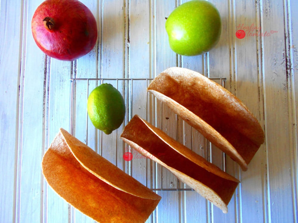 Overhead View of 3 Homemade Taco Shells Grande on a Cooling Rack with 1 Green Apple, 1 Lime and 1 Pomogranate Next to it