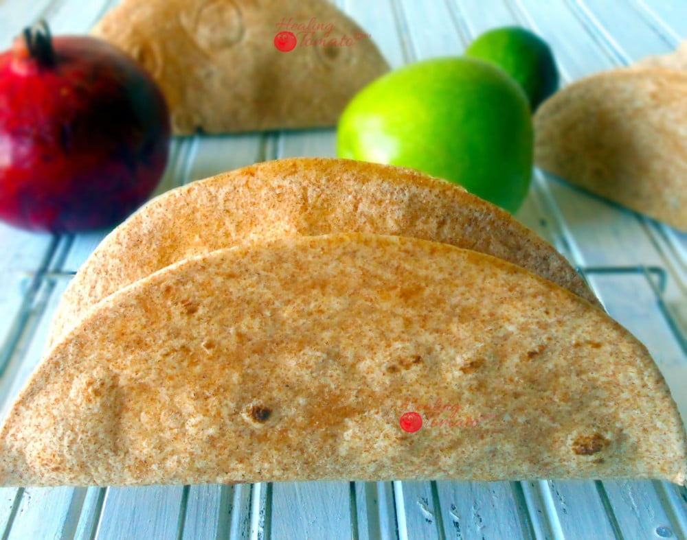 Front View of the Side of 1 Hard Taco Shell on a Cooling Rack with Pomegranate, Green Apple, Lime and 2 Taco Shells in the Background