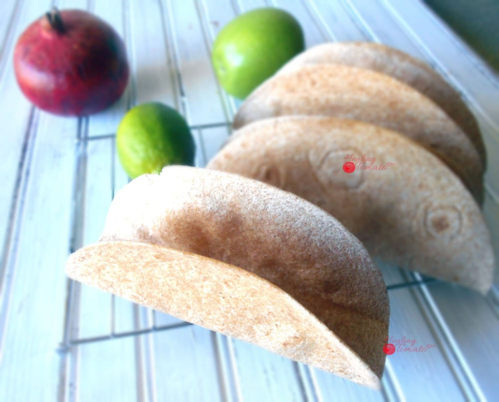 Top Angle View Homemade Taco Shells Grande on a Cooling Rack with 1 Green Apple, 1 Lime and 1 Pomegranate in the Background