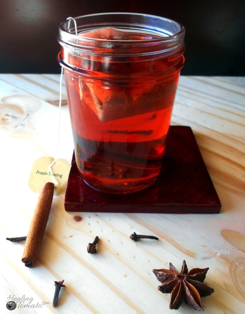 A tea bag inside a mason jar filled with hot toddy ingredients. Surrounded by cinnamon stick cloves and star anise