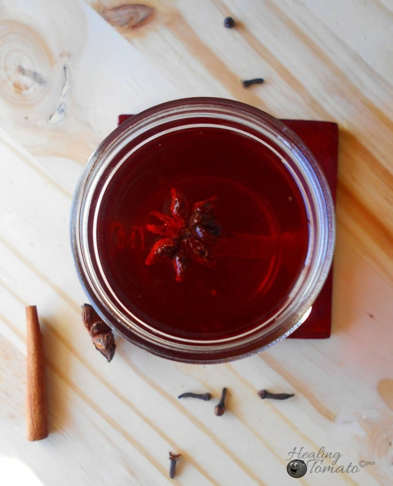 Closeup view of a tea bag inside a mason jar filled with hot toddy ingredients. Surrounded by cinnamon stick cloves and star anise
