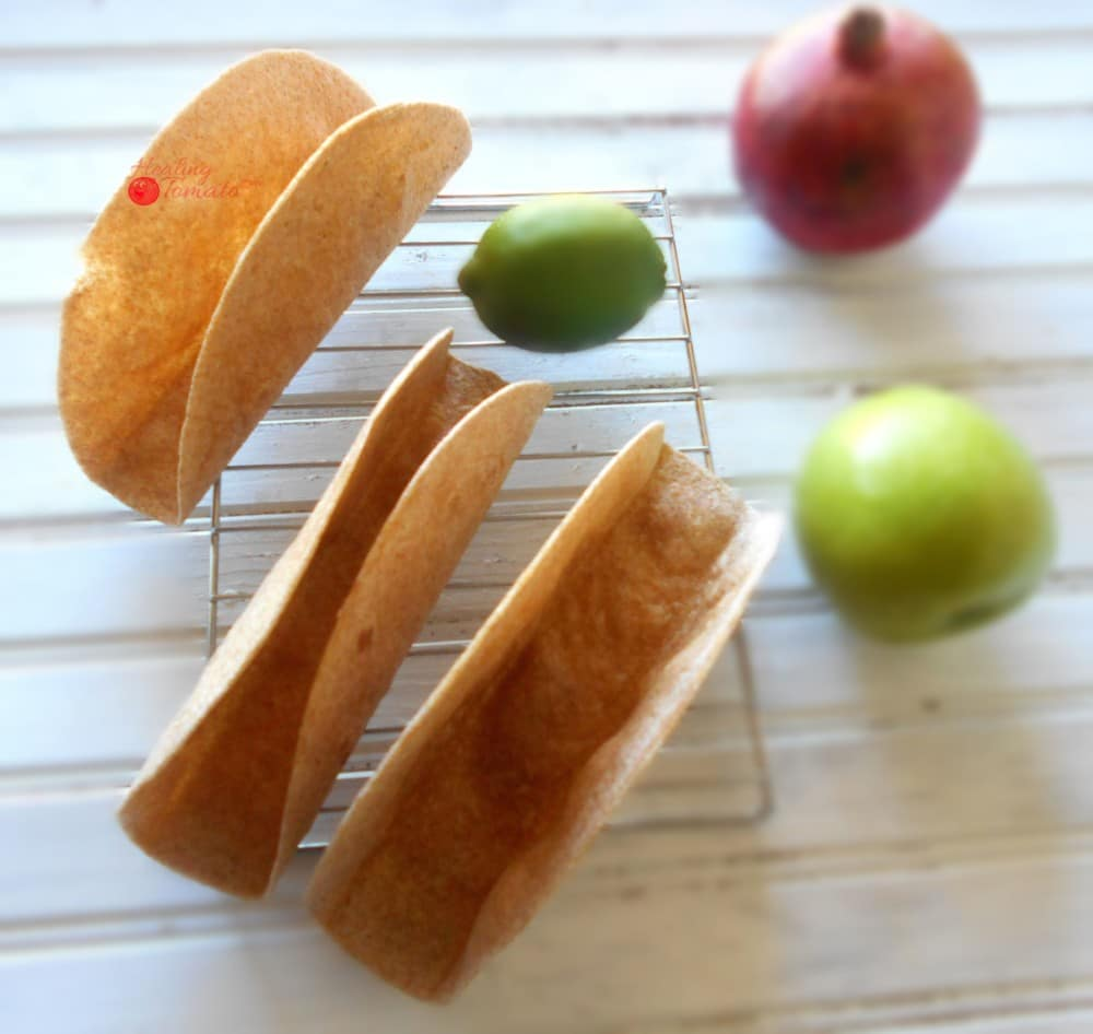 Overhead View Homemade Taco Shells Grande on a Cooling Rack with 1 Green Apple, 1 Lime and 1 Pomegranate on the Side