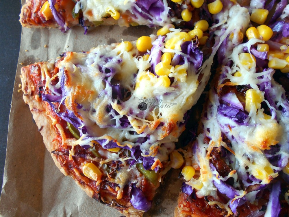 Closeup view of red cabbage pizza pie slice. Corn and melted cheese visible