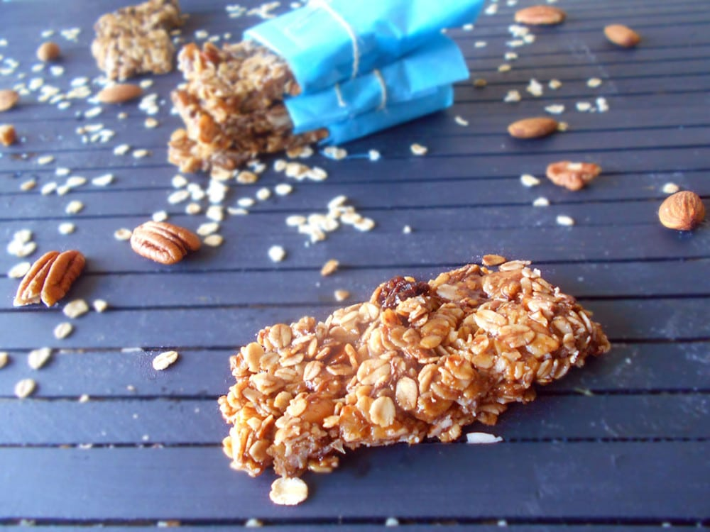 Front view of a homemade granola bar. More granola bars in the back with pecans and oatmeal scattred