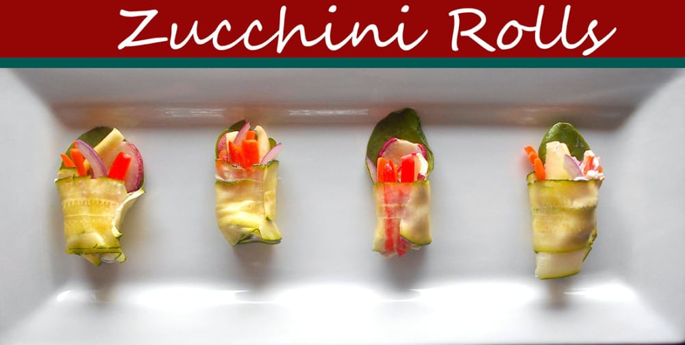 Overhead view of 4 zucchini rolls on a white plate
