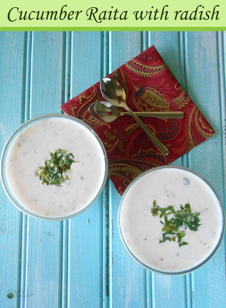 2 glass bowls filled with cucumber raita and garnished with cilantro. Two small spoons on a red decorative napkin placed next to bowls