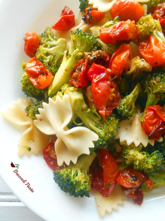 Closeup view of a white plate filled with roasted cherry tomatoes, broccoli and bow tie pasta
