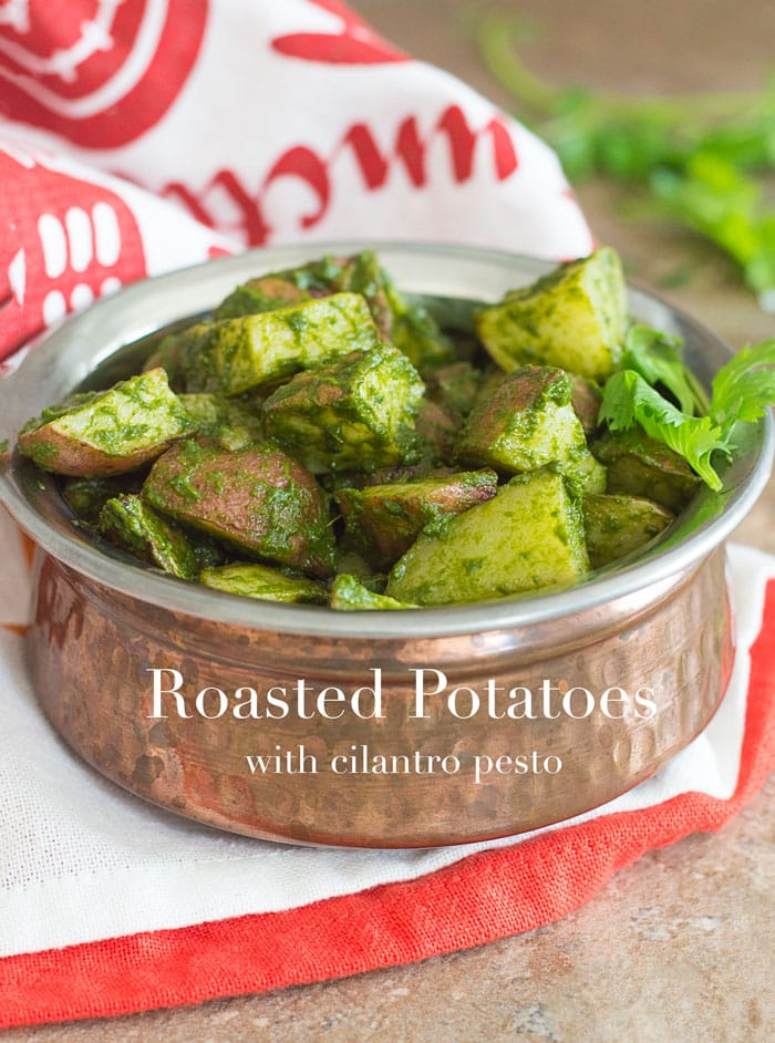 Front View of Roasted Potatoes in Cilantro Pesto. Roasted Potatoes are in a Copper Bowl Under a white and Orange Kitchen Towel with Sprigs of Cilantro in the Distant Background