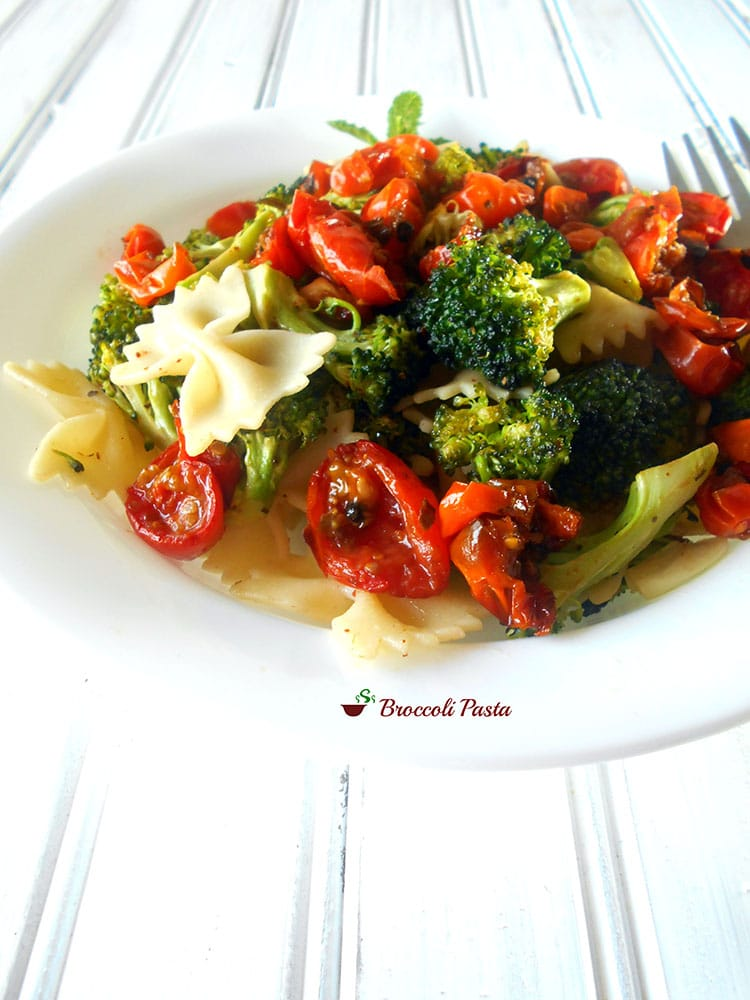Front view of a white plate filled with roasted cherry tomatoes, broccoli and bow tie pasta
