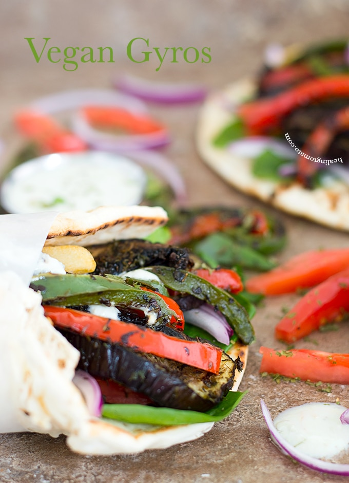 Side View of a Wrapped Pita Filled with Grilled Veggies. In the Background, There is an Open Flatbread Filled with Grilled Veggies. Onions and Tomatoes strewn about