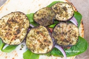 grilled eggplants topped on the tomatoes and onions - vegan gyros