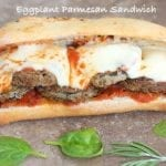 Front View of an Eggplant Sandwich with Melted Mozzarella Cheese and Surrounded by Spinach Leaves and Rosemary Sprigs
